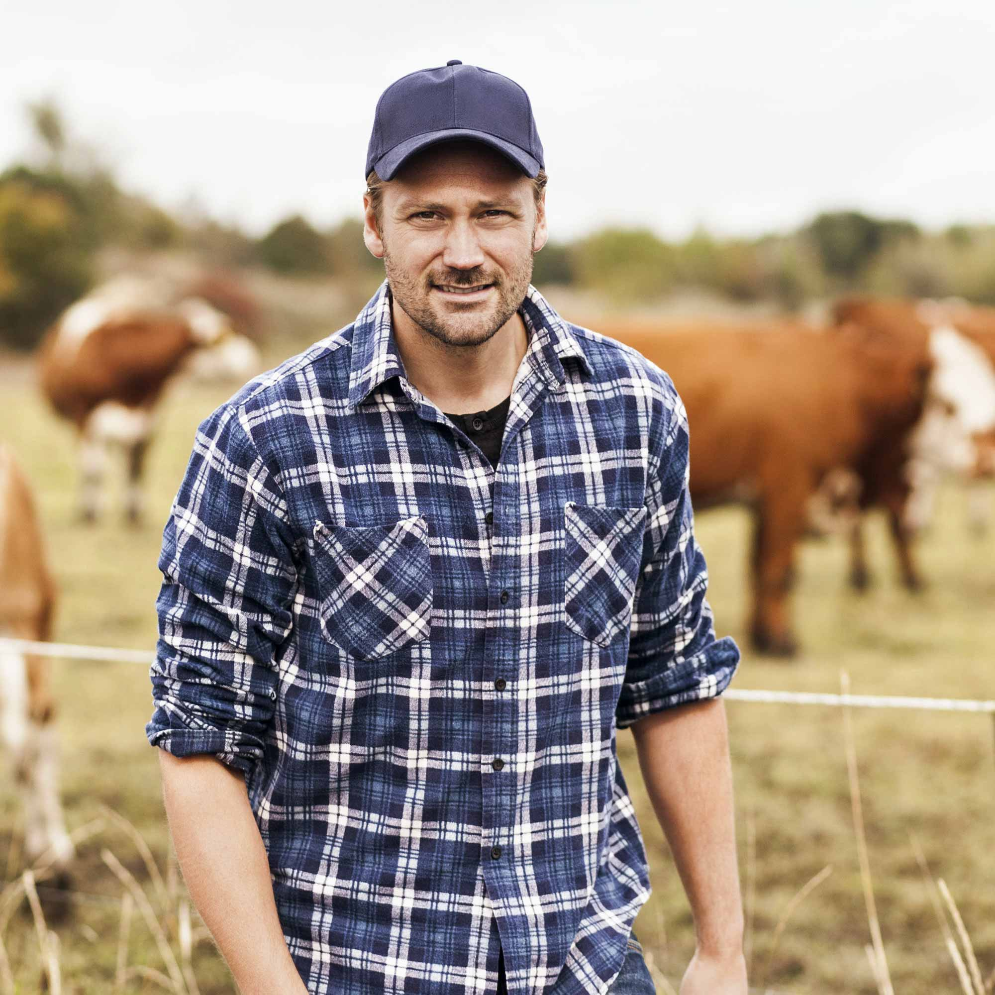 Farmer man in front of cows